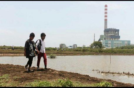 Dua orang anak berjalan di kawasan pembangkit listrik tenaga uap (PLTU) Cirebon I di Desa Kanci. {Gambar: Donny Iqbal}