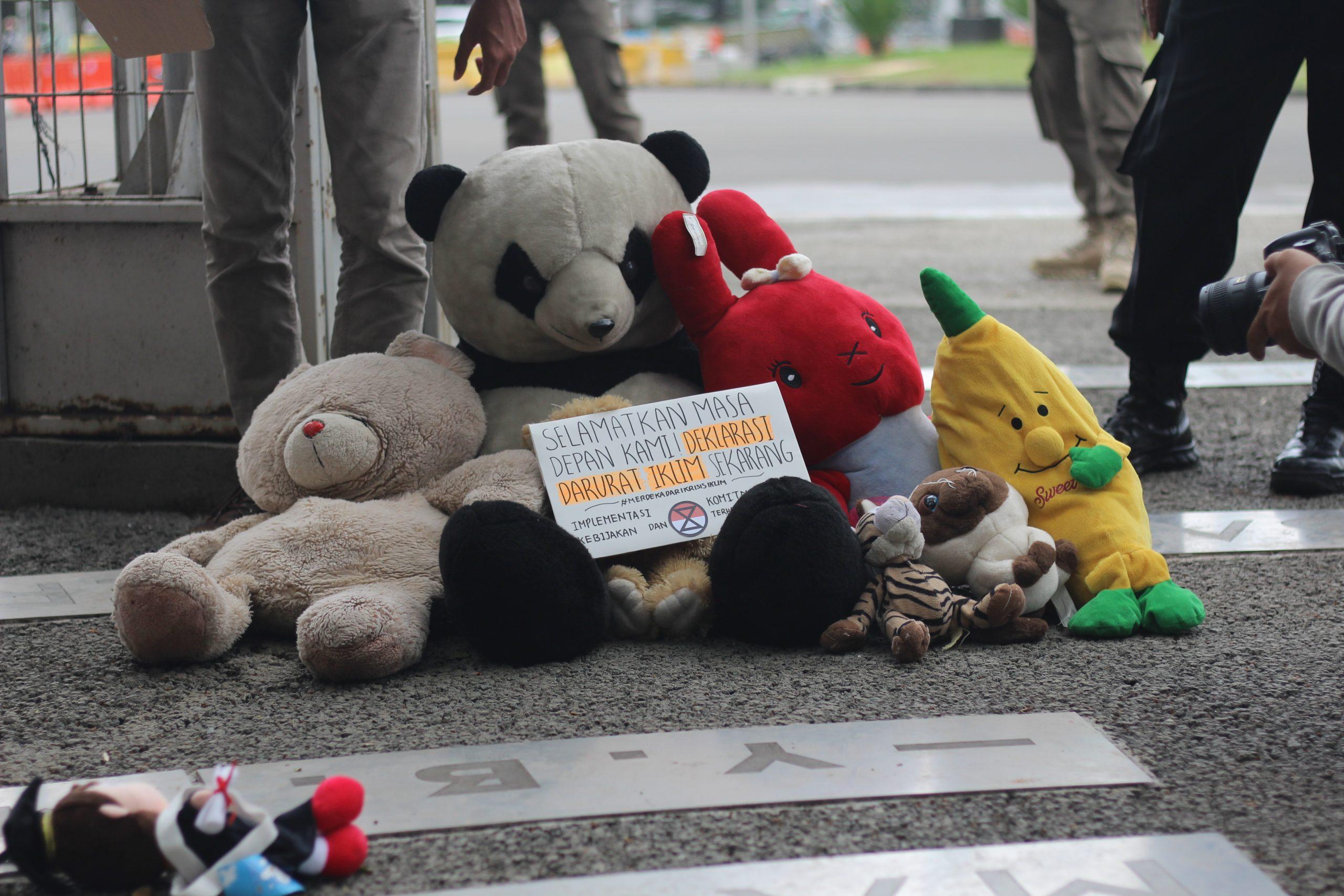 [:en]Extinction Rebellion Indonesia meletakkan pesan di antara mainan anak dalam aksi yang dilakukan bertepatan dengan Hari Anak Sedunia (20/11/2020). Sumber: XR Indonesia[:]
